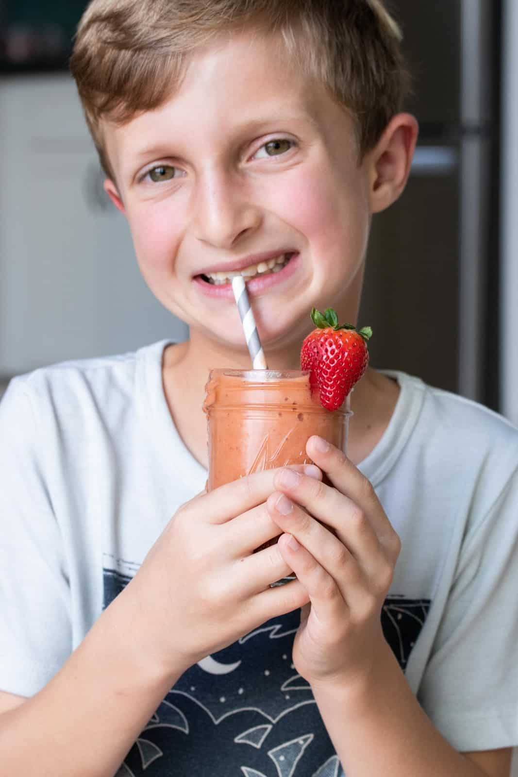 Boy drinking a salmon colored smoothie from a grey striped straw