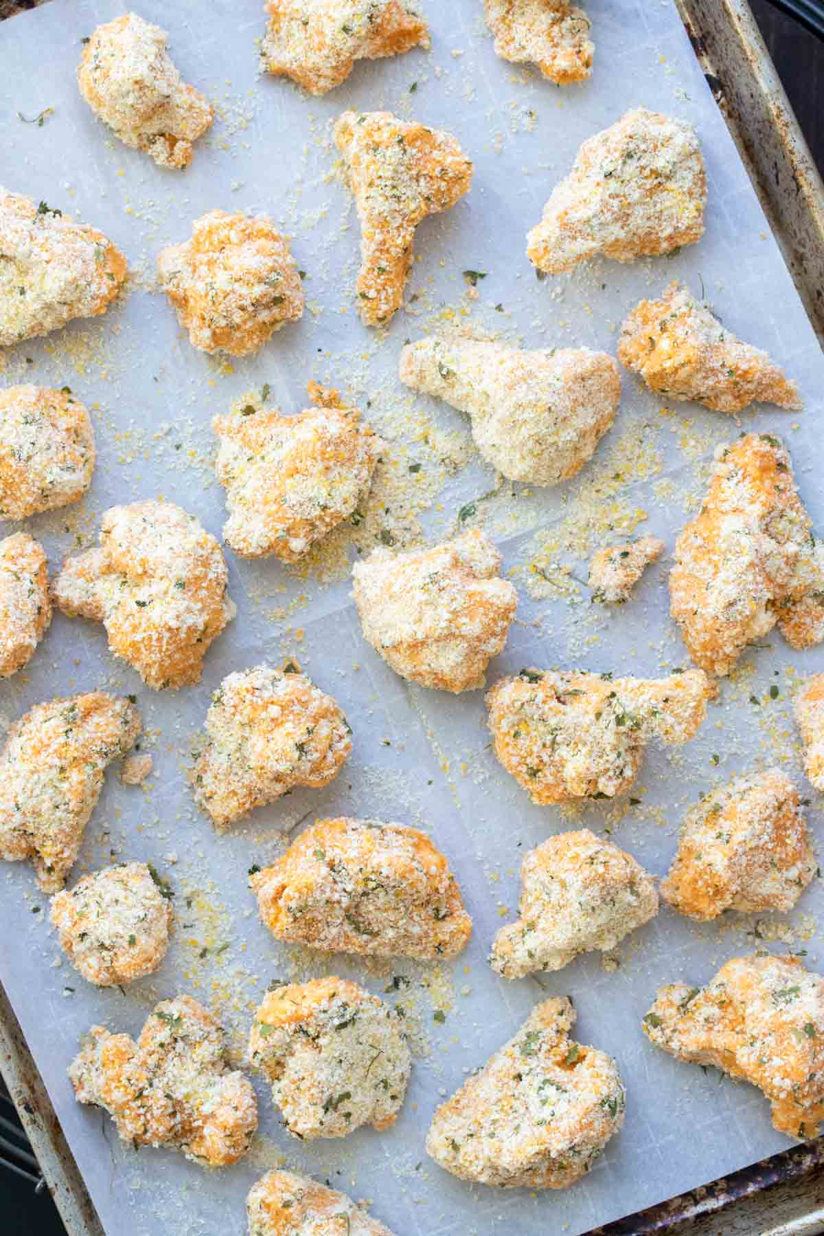Breadcrumb coated cauliflower pieces on a baking sheet