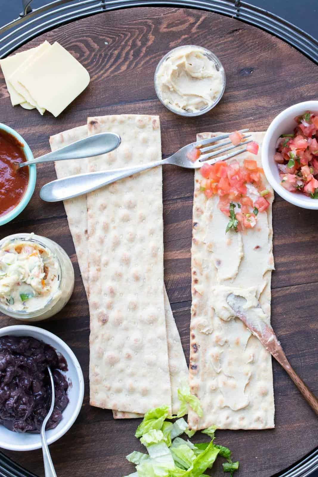 Knife spreading cream cheese and fork spreading salsa on slices of lavash bread