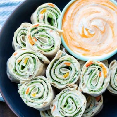 Black plate with pinwheel rolls ups filled with lettuce, salsa and cream cheese