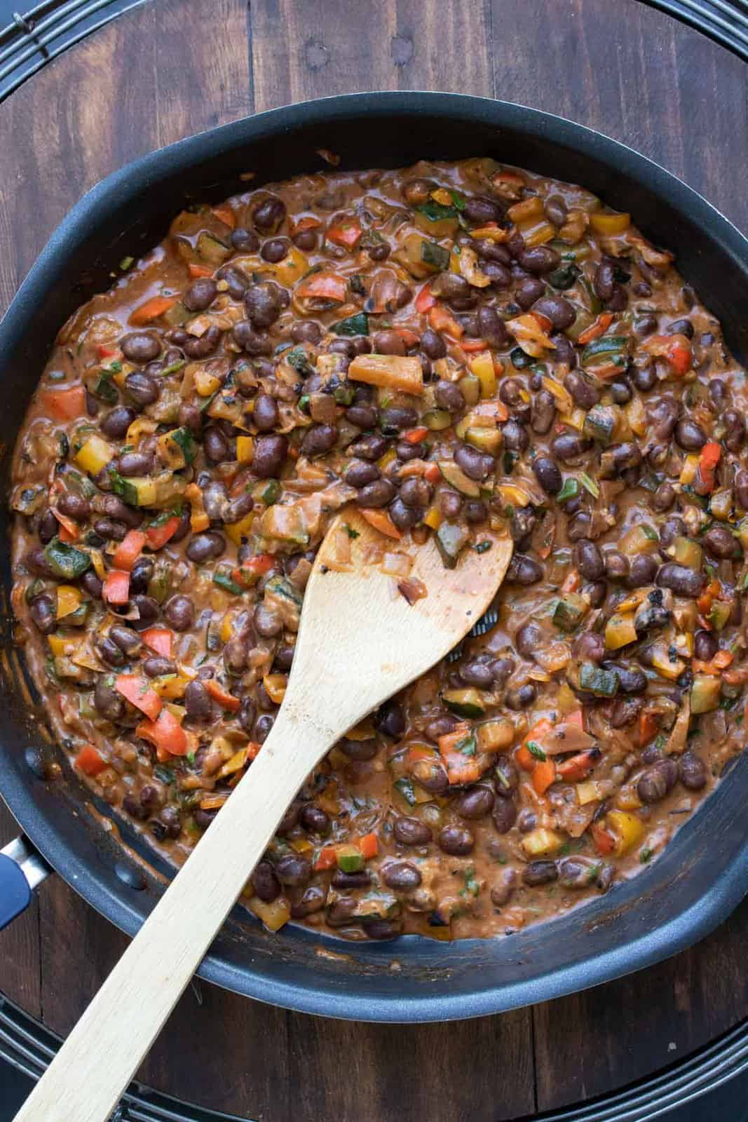 Wooden spoon mixing black bean mixture with veggies in a pan