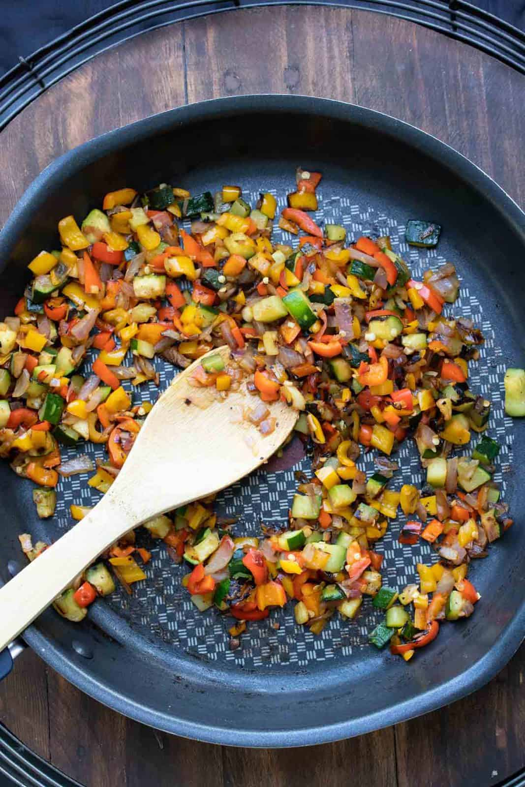 Wooden spoon mixing chopped veggies in a pan