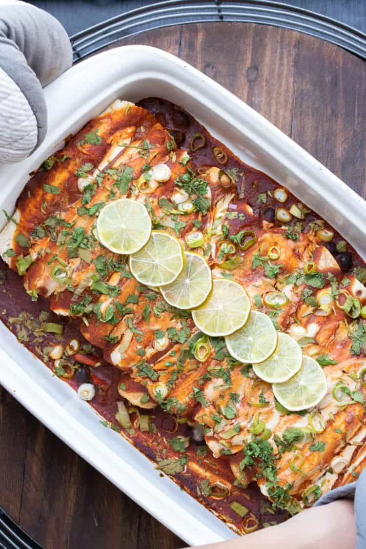 Baked enchiladas with red sauce topped with green onions and limes