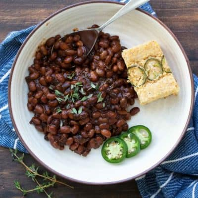 Cream plate with baked beans, jalapeno slices and cornbread