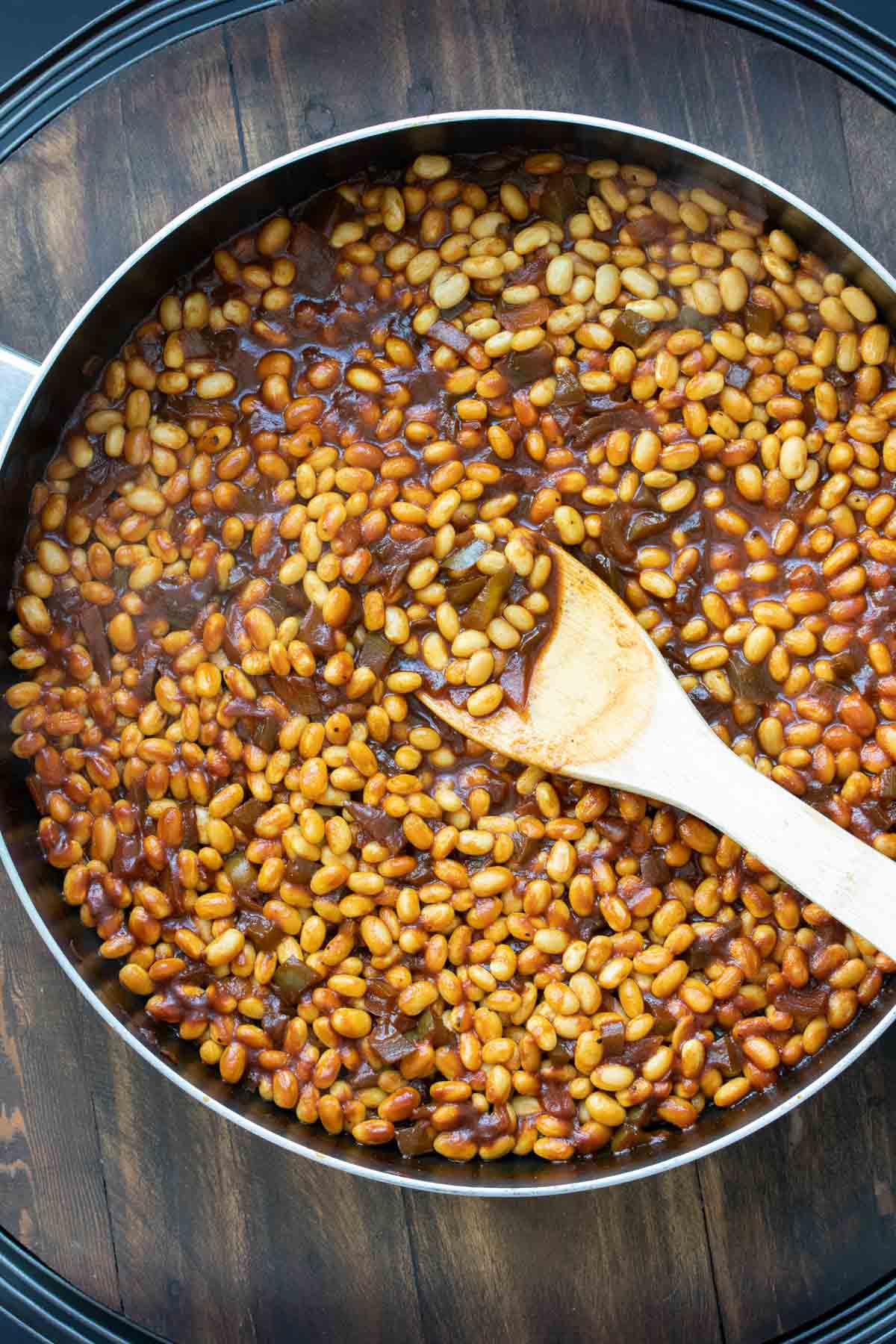 Beans in a pan with ingredients for a baked bean sauce
