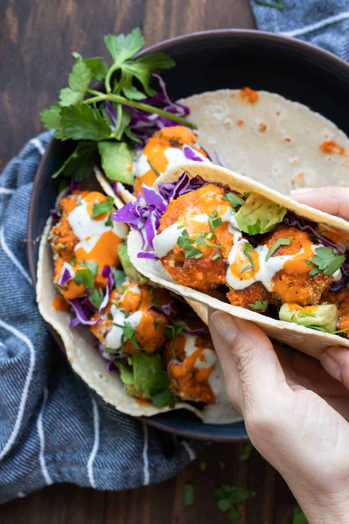 Hand holding a crispy buffalo cauliflower taco with toppings
