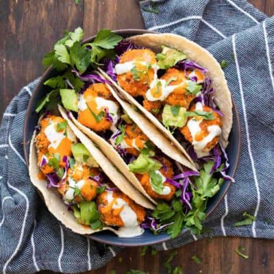 Craving comfort food? These buffalo cauliflower tacos are the perfect solution for a crispy baked, veggie filled, wrapped in a tortilla kind of meal! #vegantacos #healthycomfortfood