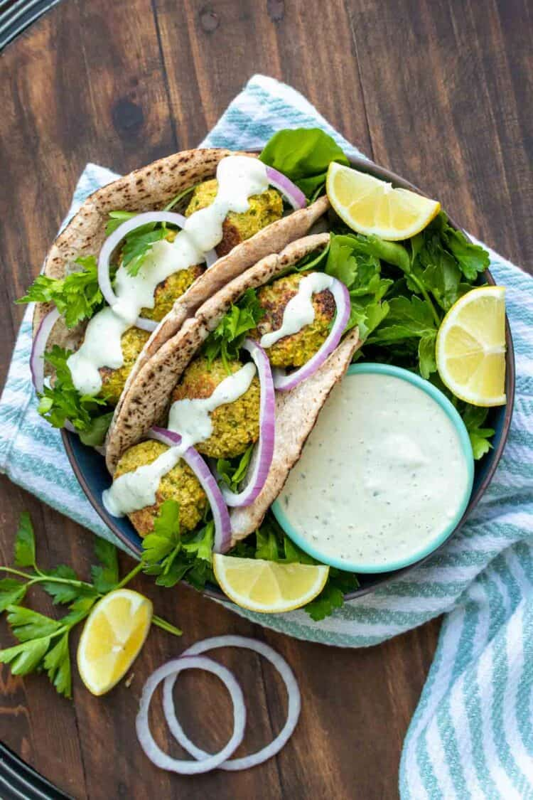 Two falafel pita sandwiches on a plate next to ranch dip
