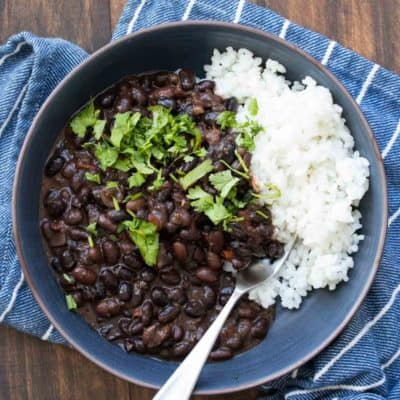 Blue bowl with cooked black beans over white rice