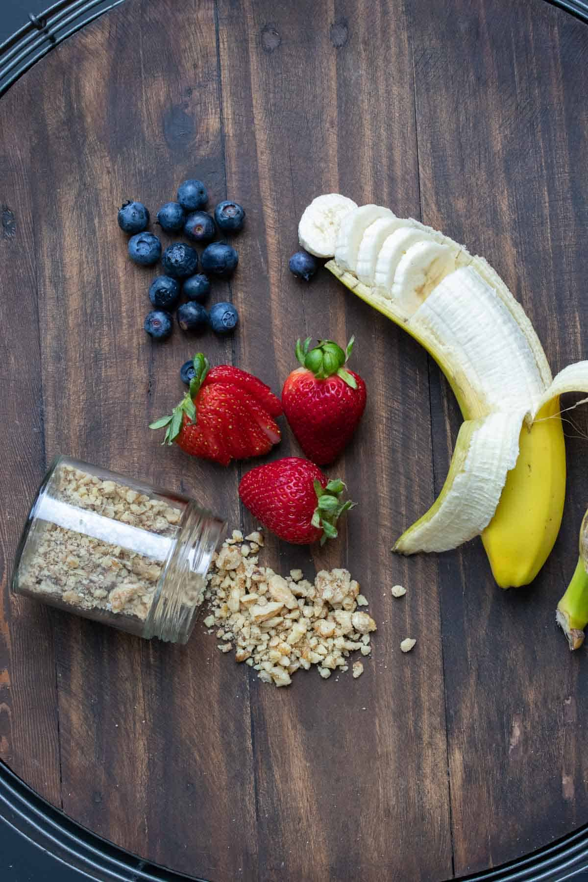 Fruit and nuts to top oatmeal with on a wooden surface