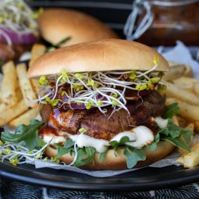 Portobello mushroom burger on a bun with lettuce, sprouts and sauce
