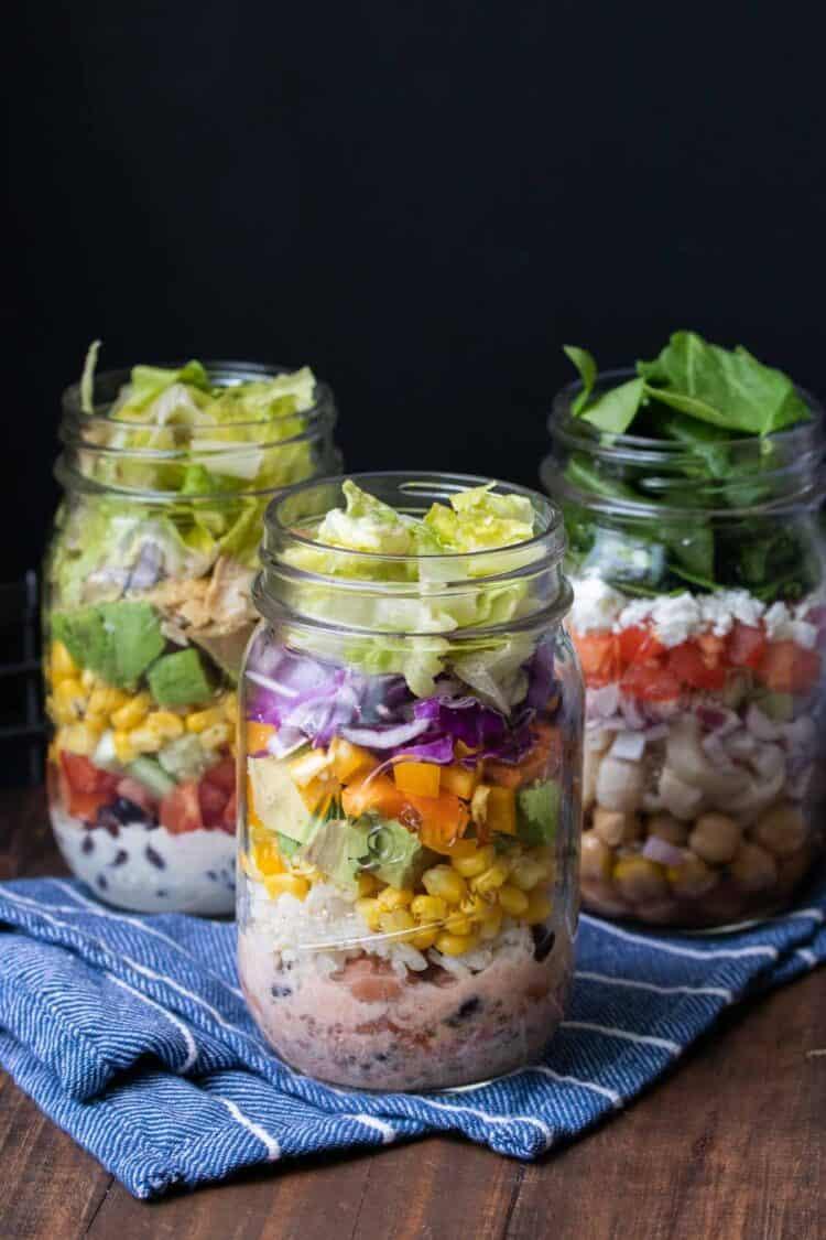 Three types of mason jar salads on a blue kitchen towel