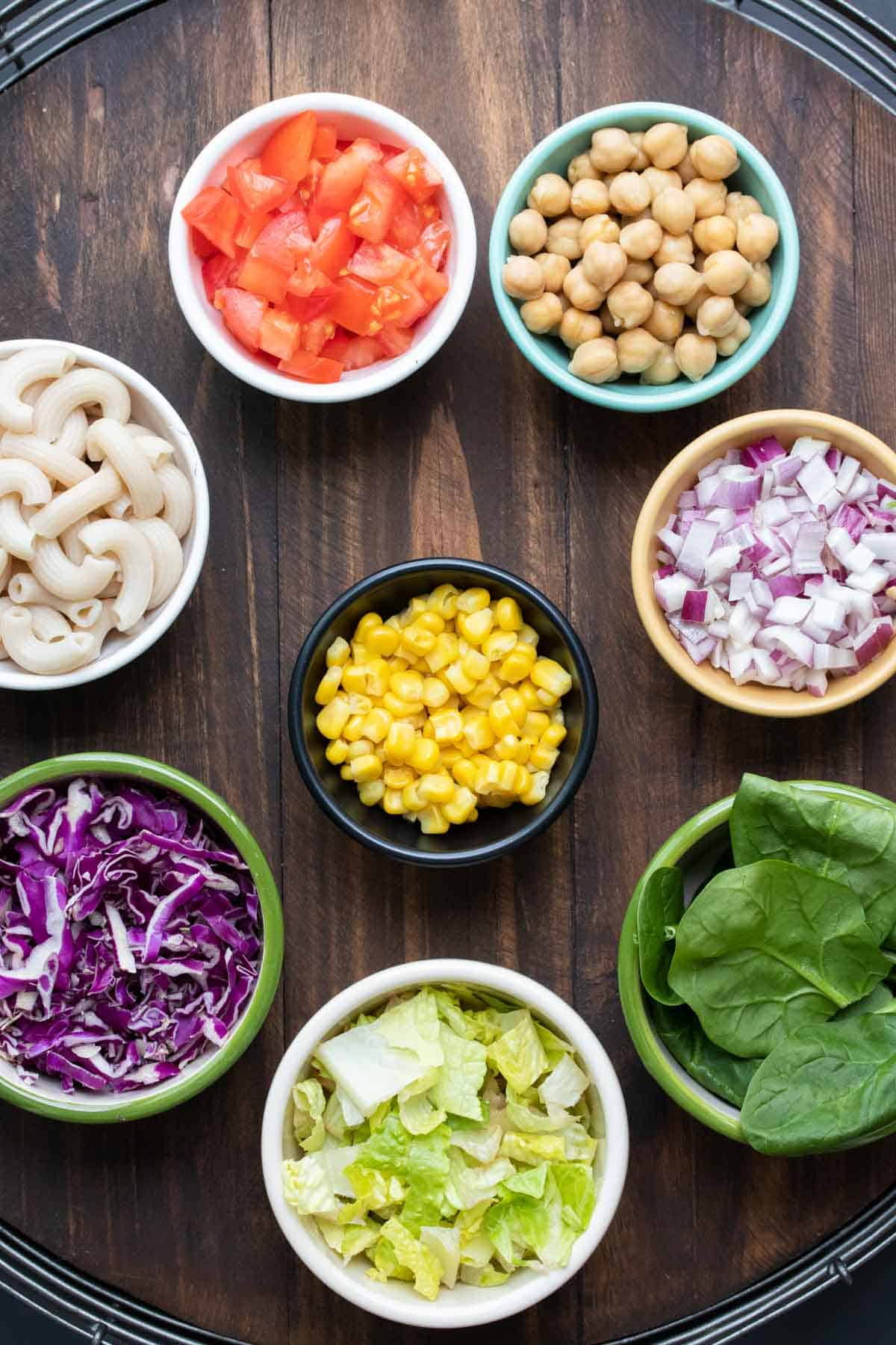 Colorful bowls with salad ingredients on a wooden surface