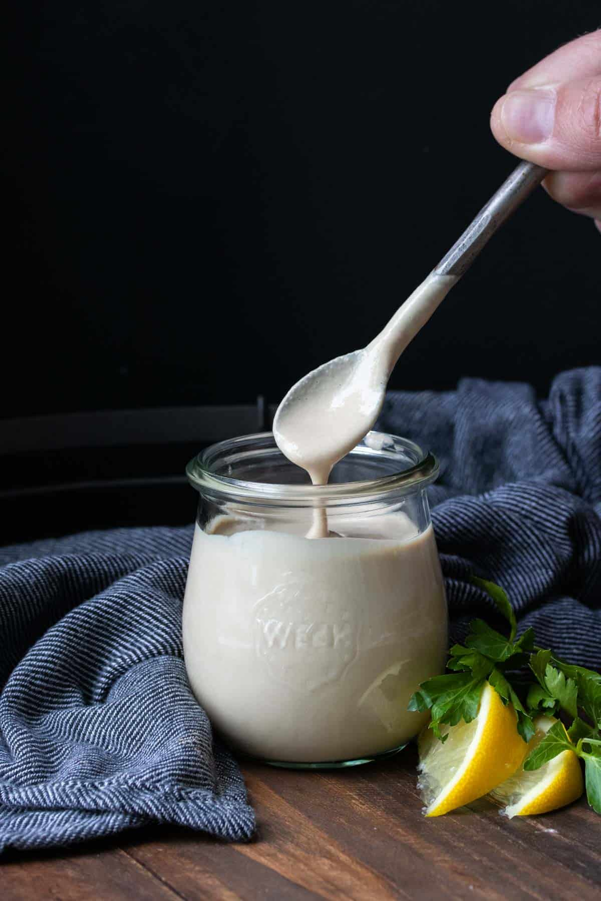 Spoon dripping with creamy tahini sauce over a glass jar