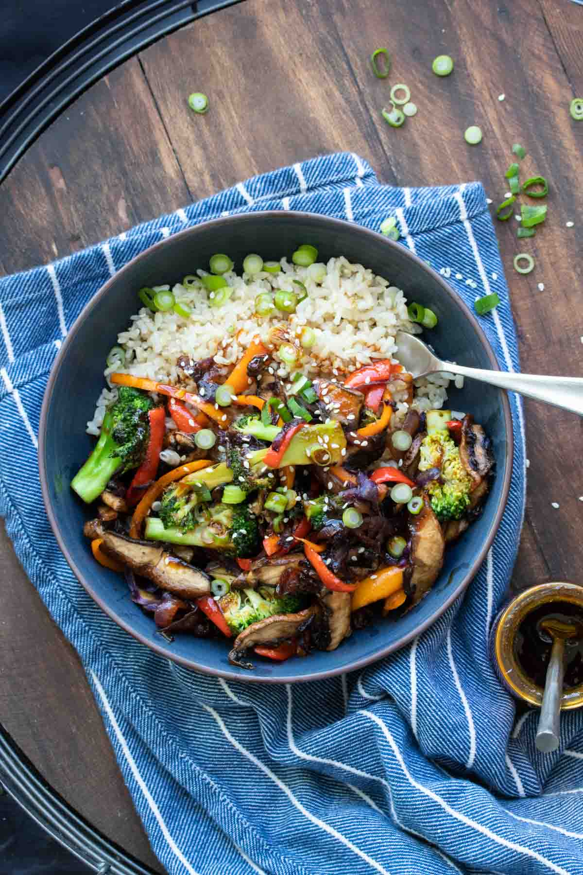 Black bowl filled with rice topped with teriyaki vegetable stir fry