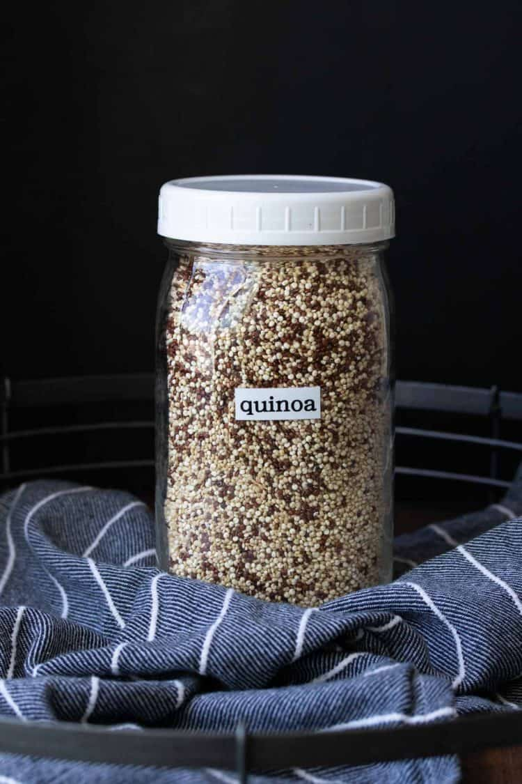 Glass jar with white lid filled with dry quinoa