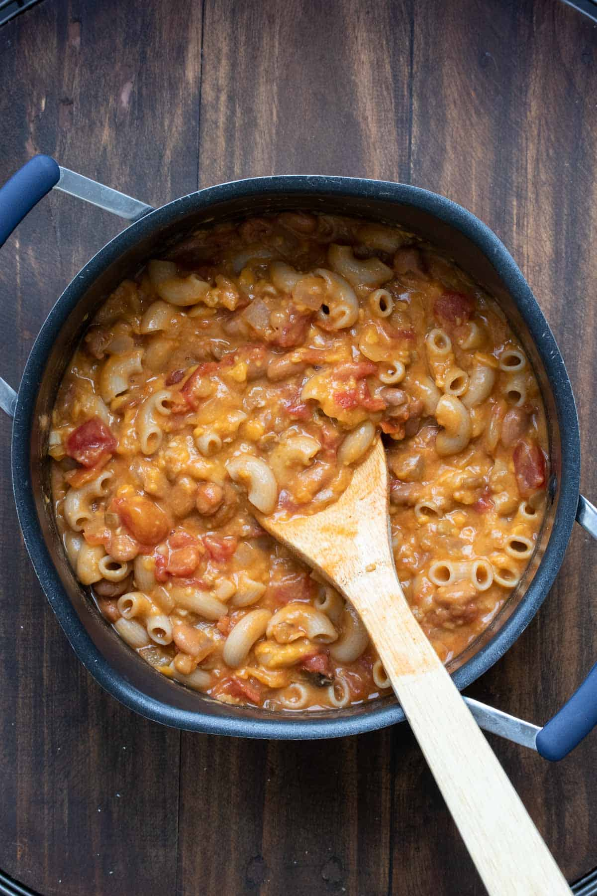 Wooden spoon mixing cheese sauce into a pot of chili mac