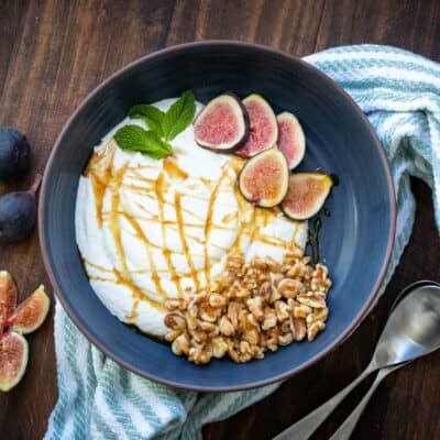 Dark grey blue bowl with yogurt inside topped with figs and walnuts