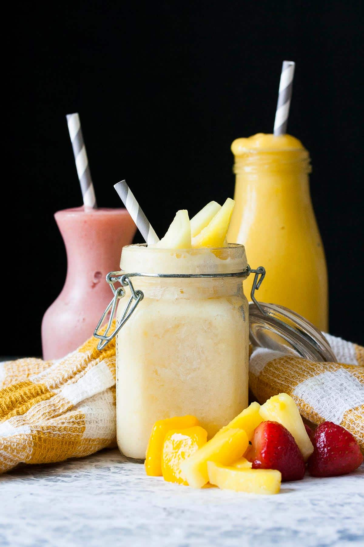 Three different glass jars filled with different colored fruit smoothies