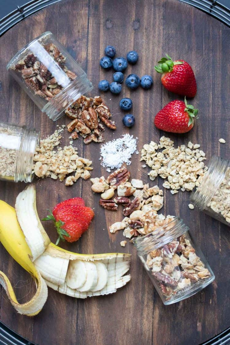 Smoothie bowl toppings like nuts and fruit spread out on a wooden surface