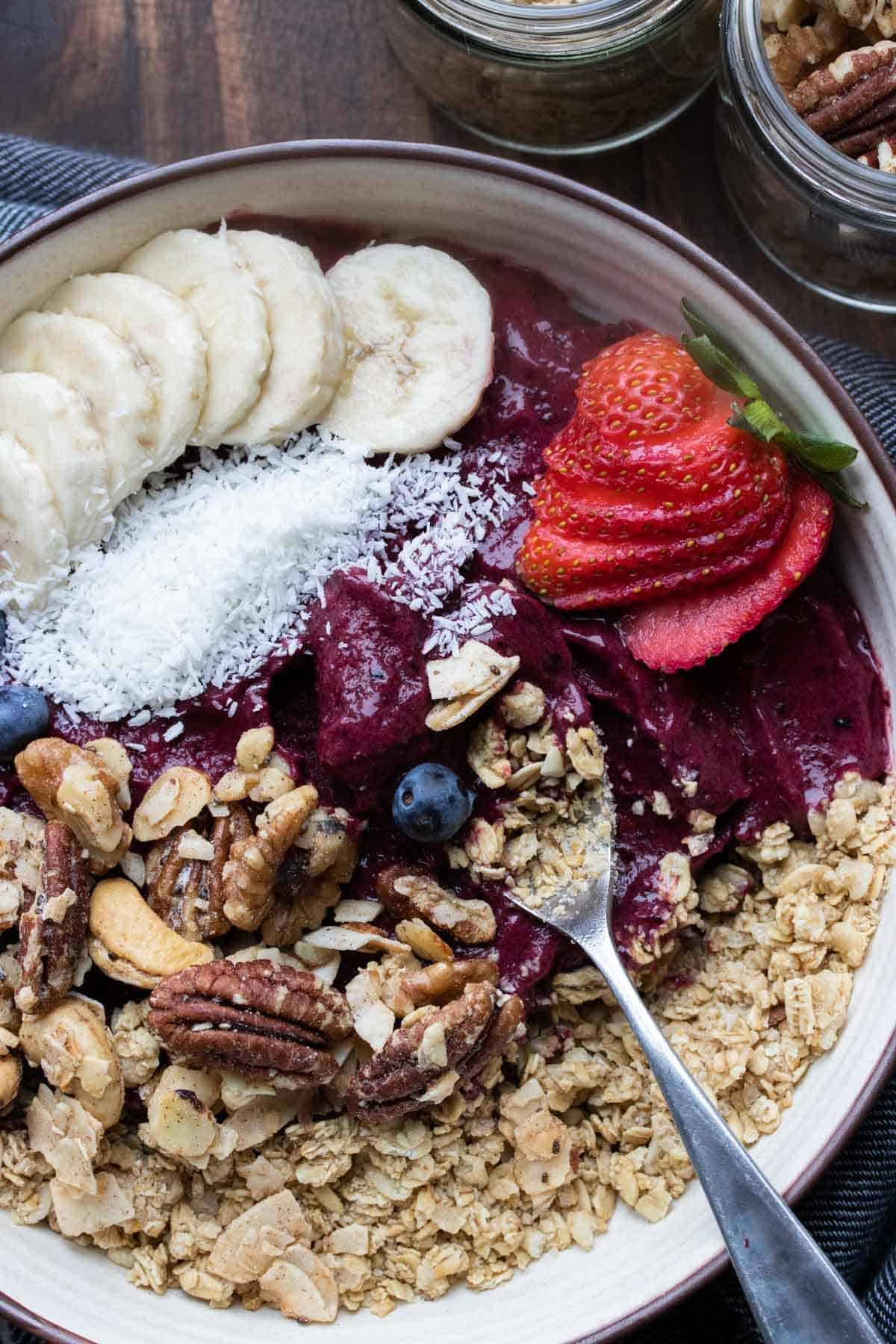 Spoon getting a bite of a smoothie bowl loaded with toppings