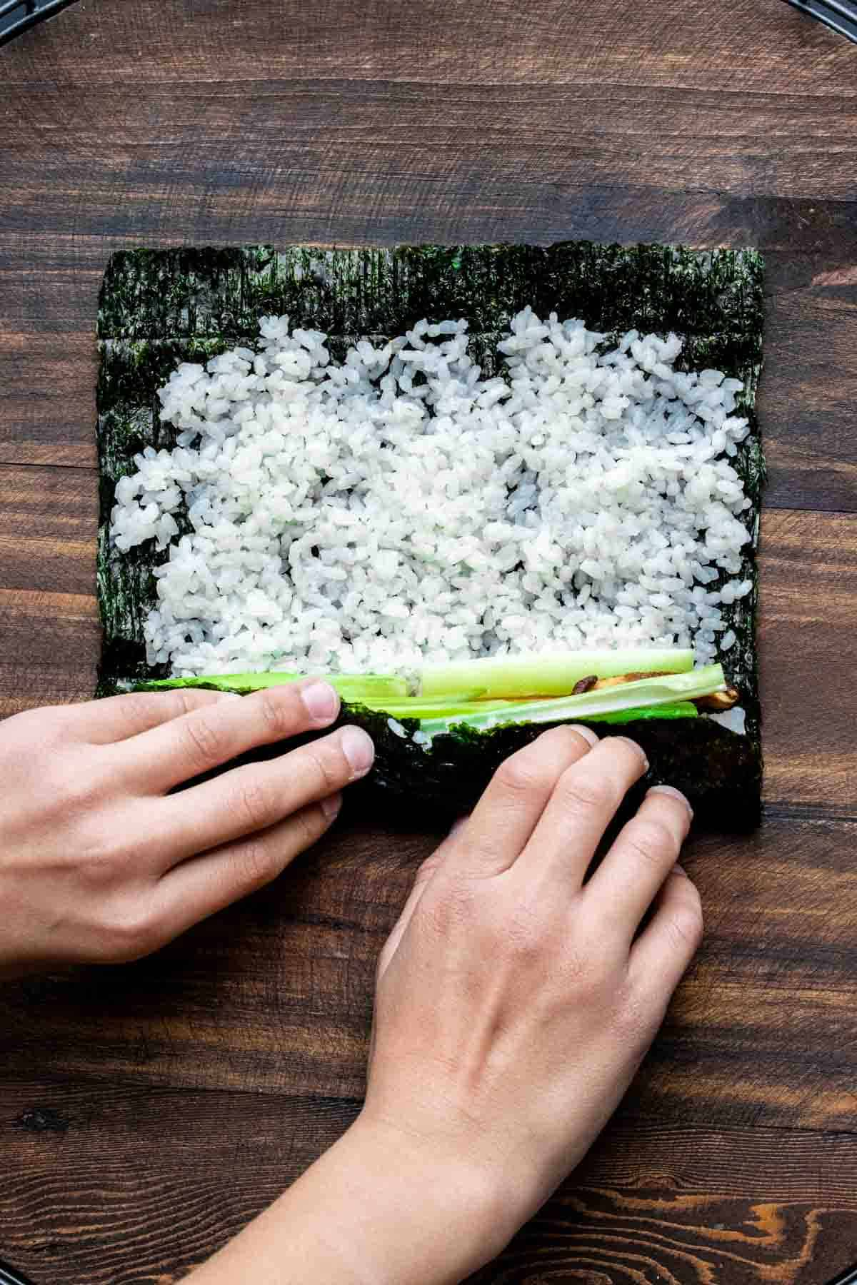 Two hand rolling up a veggie sushi roll