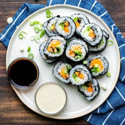 Veggie sushi rolls cut up and piled on a cream plate