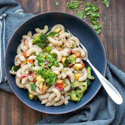 A black bowl of vegetable pasta salad with a fork in it