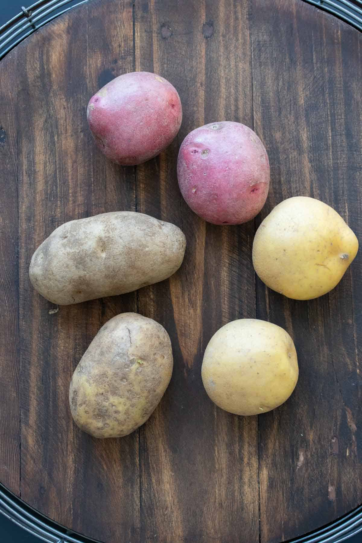Top view of different kinds of potatoes on a wooden table