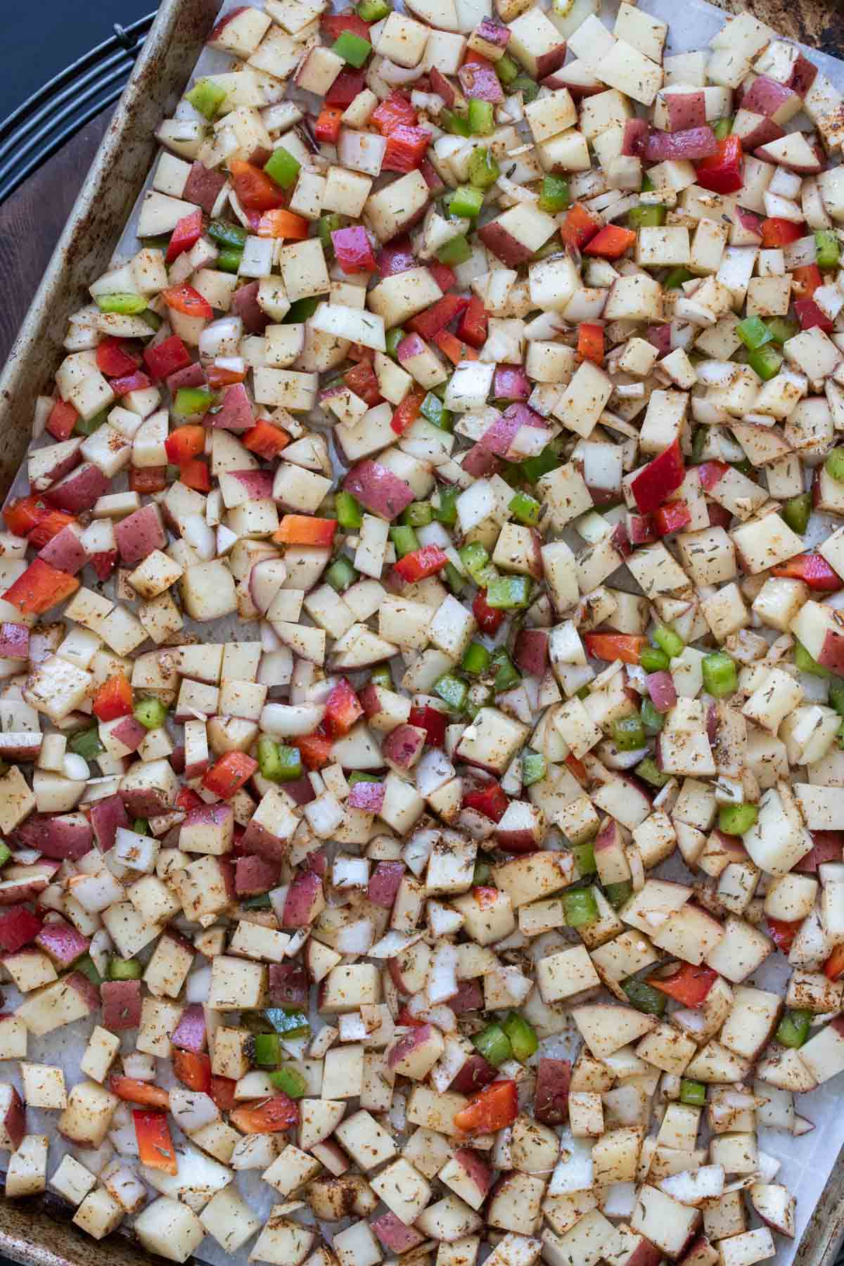 Chopped potatoes, onions and peppers on a baking sheet
