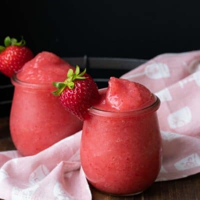 Glasses filled with bright pink blended frose drink and a strawberry