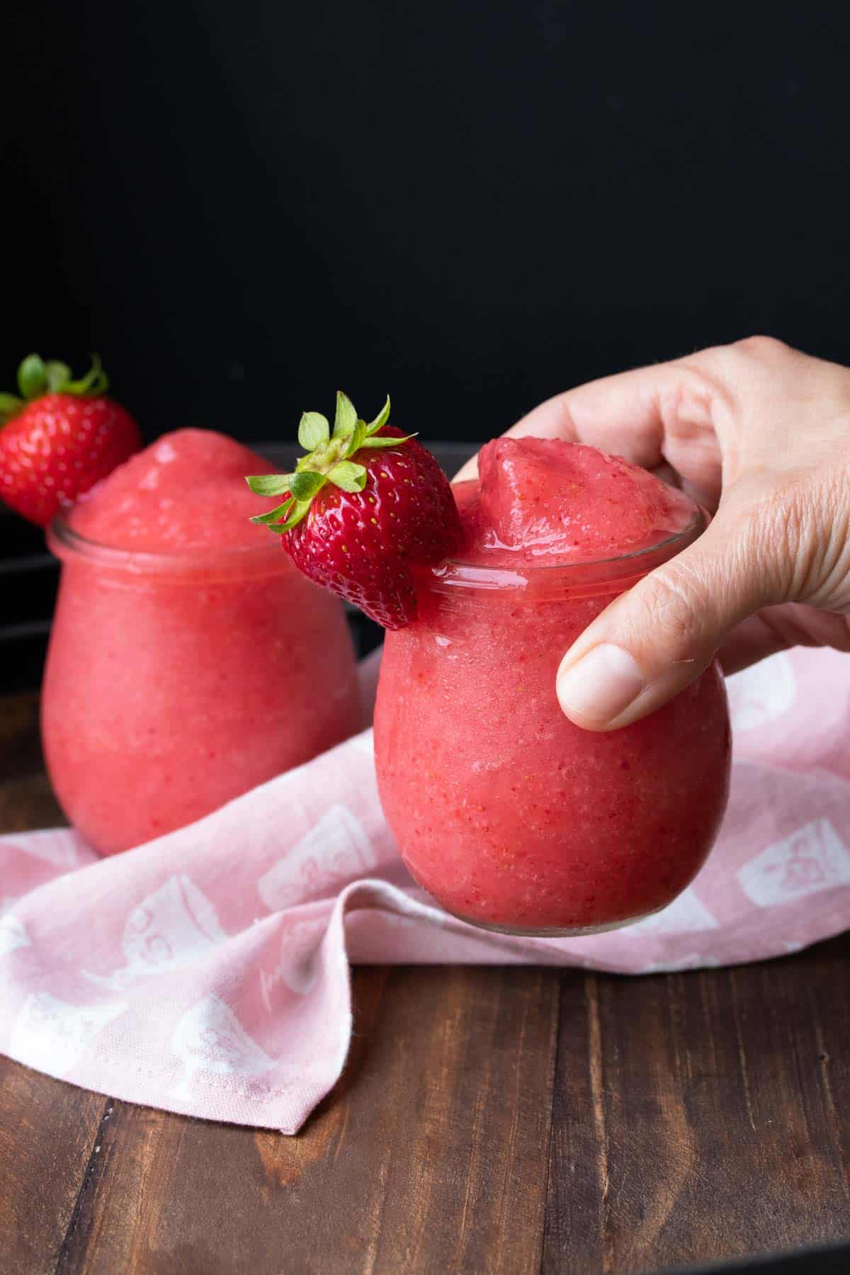 Hand holding a glass of bright pink frose drink