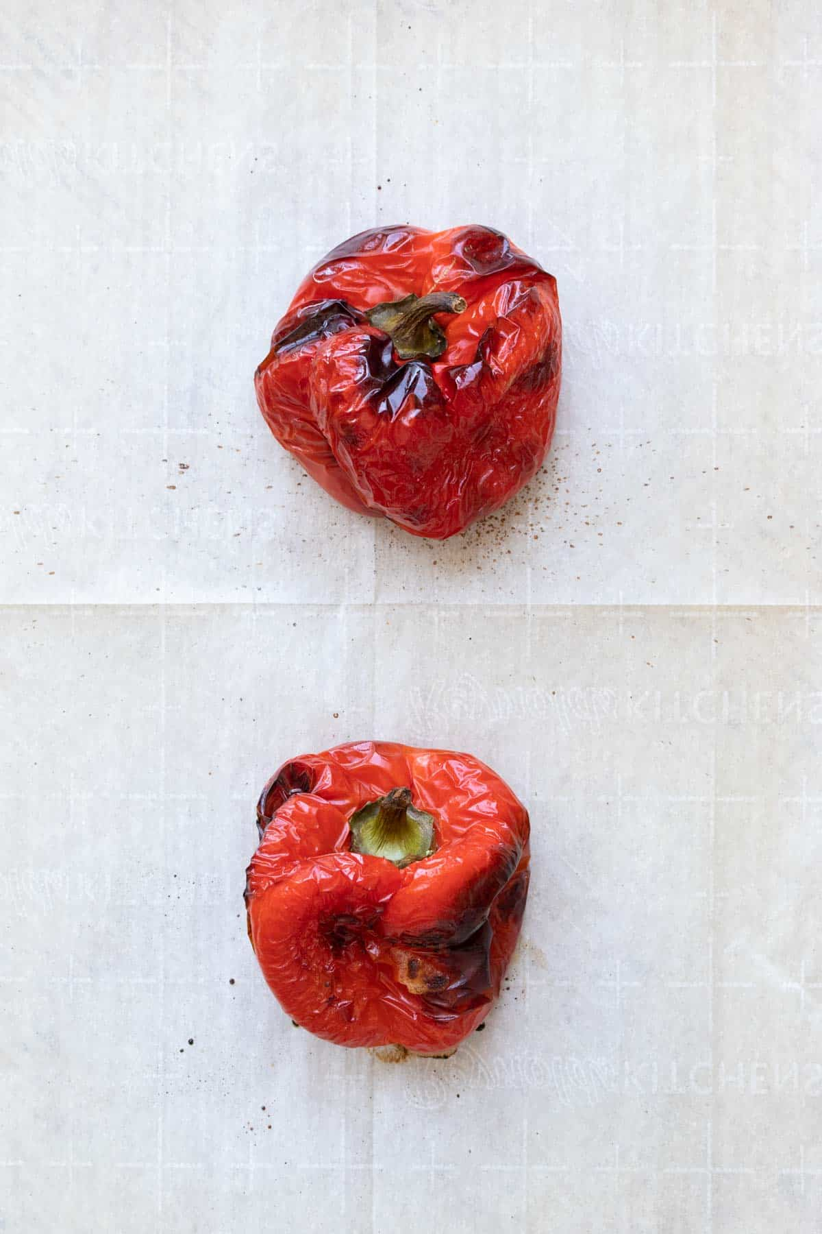 Two roasted red peppers on parchment paper