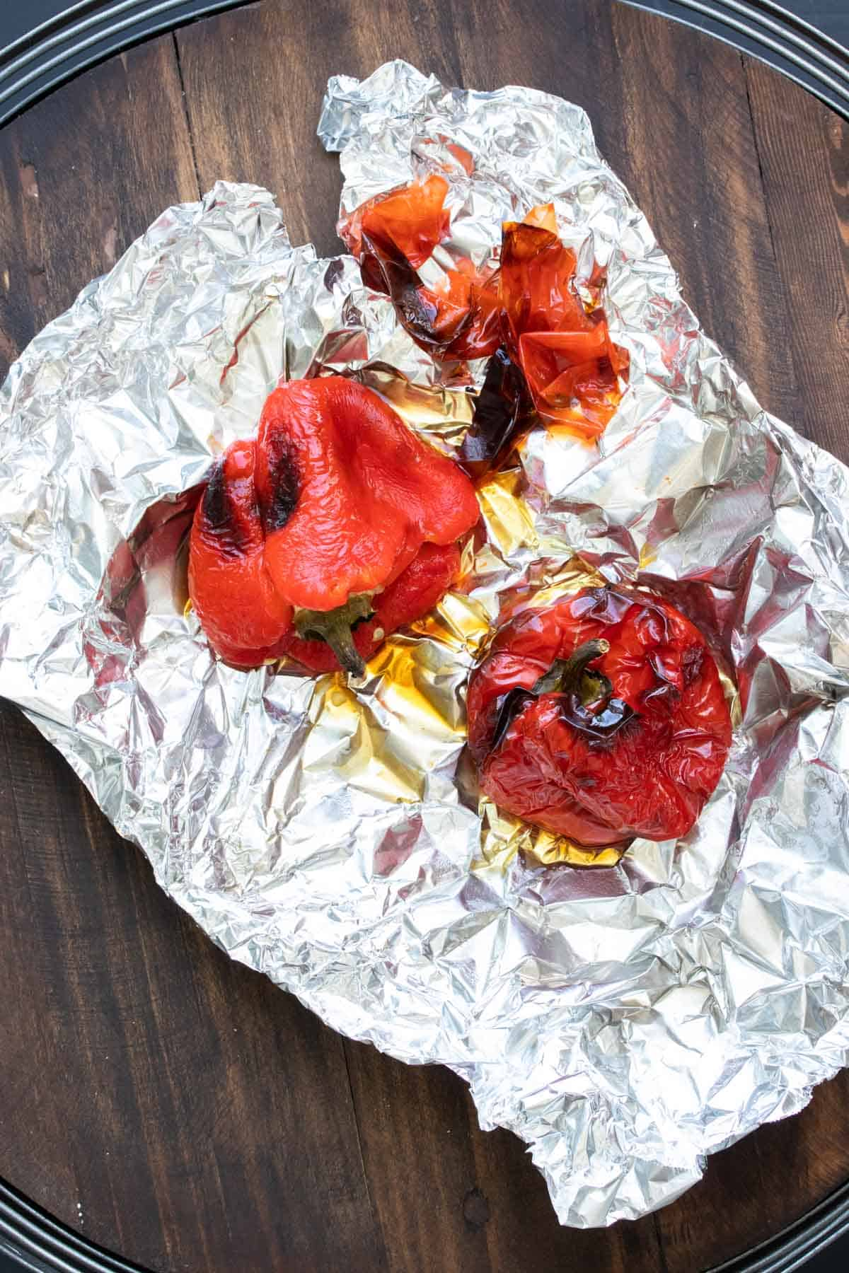 Tin foil with two roasted red peppers on it