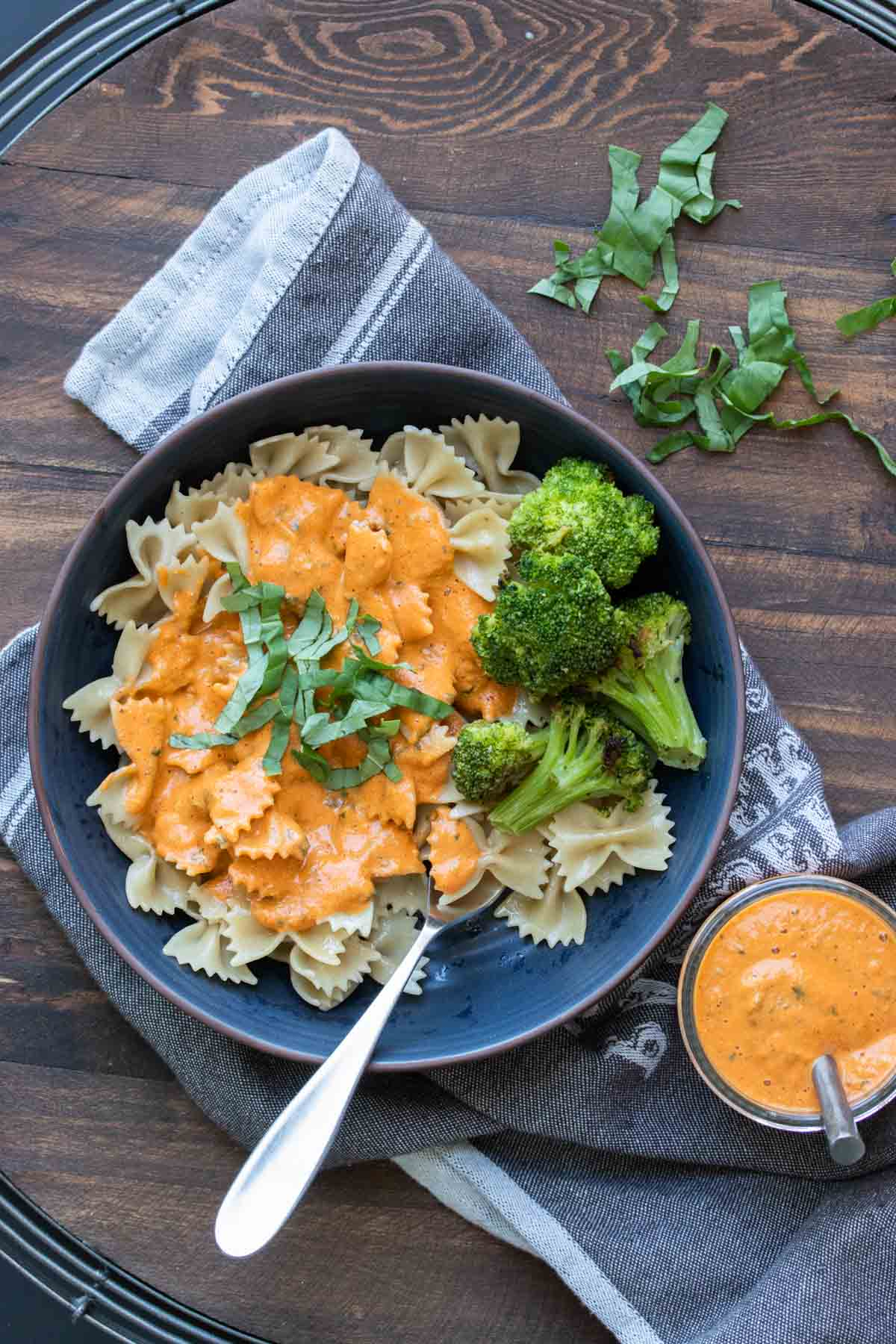 Dark blue plate with farfale pasta topped with roasted red pepper sauce and broccoli