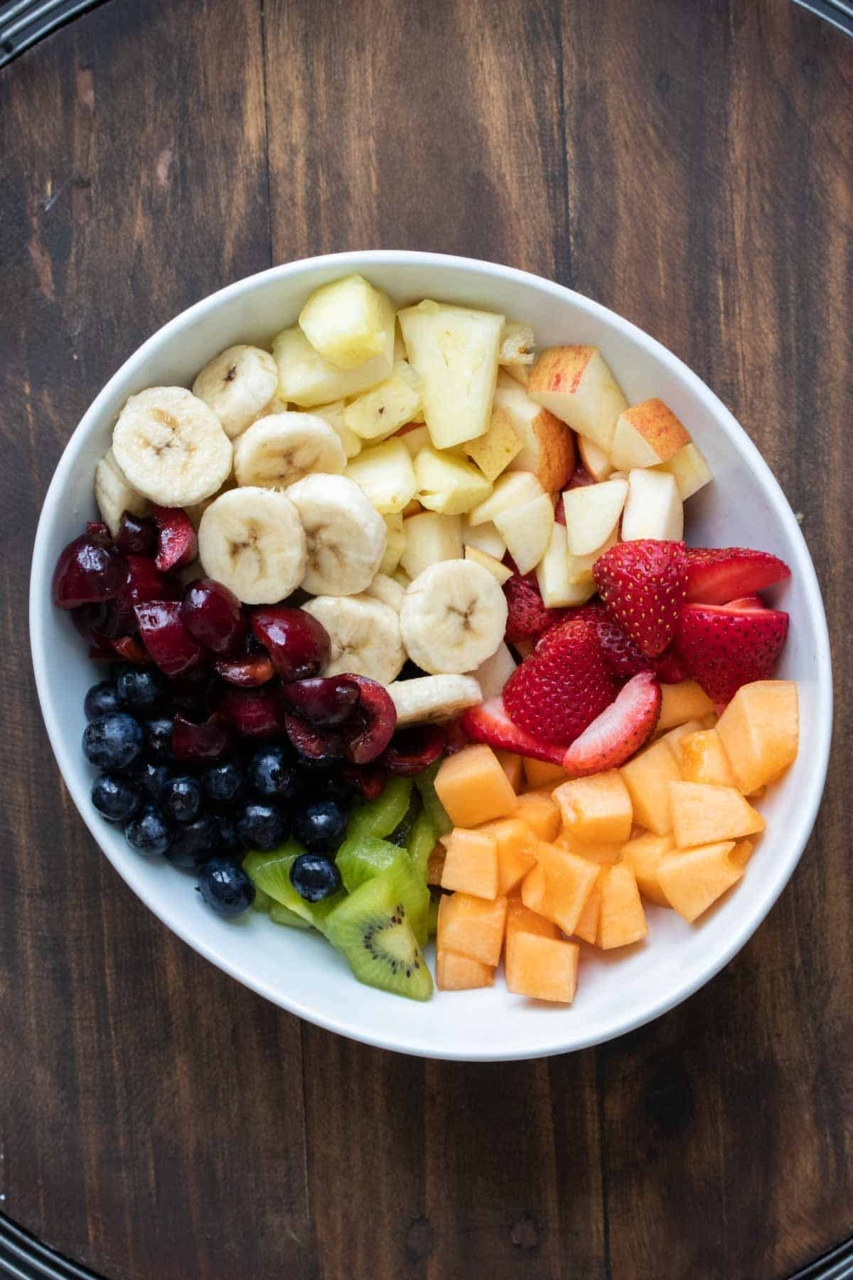 White bowl with sections of cut up fruit