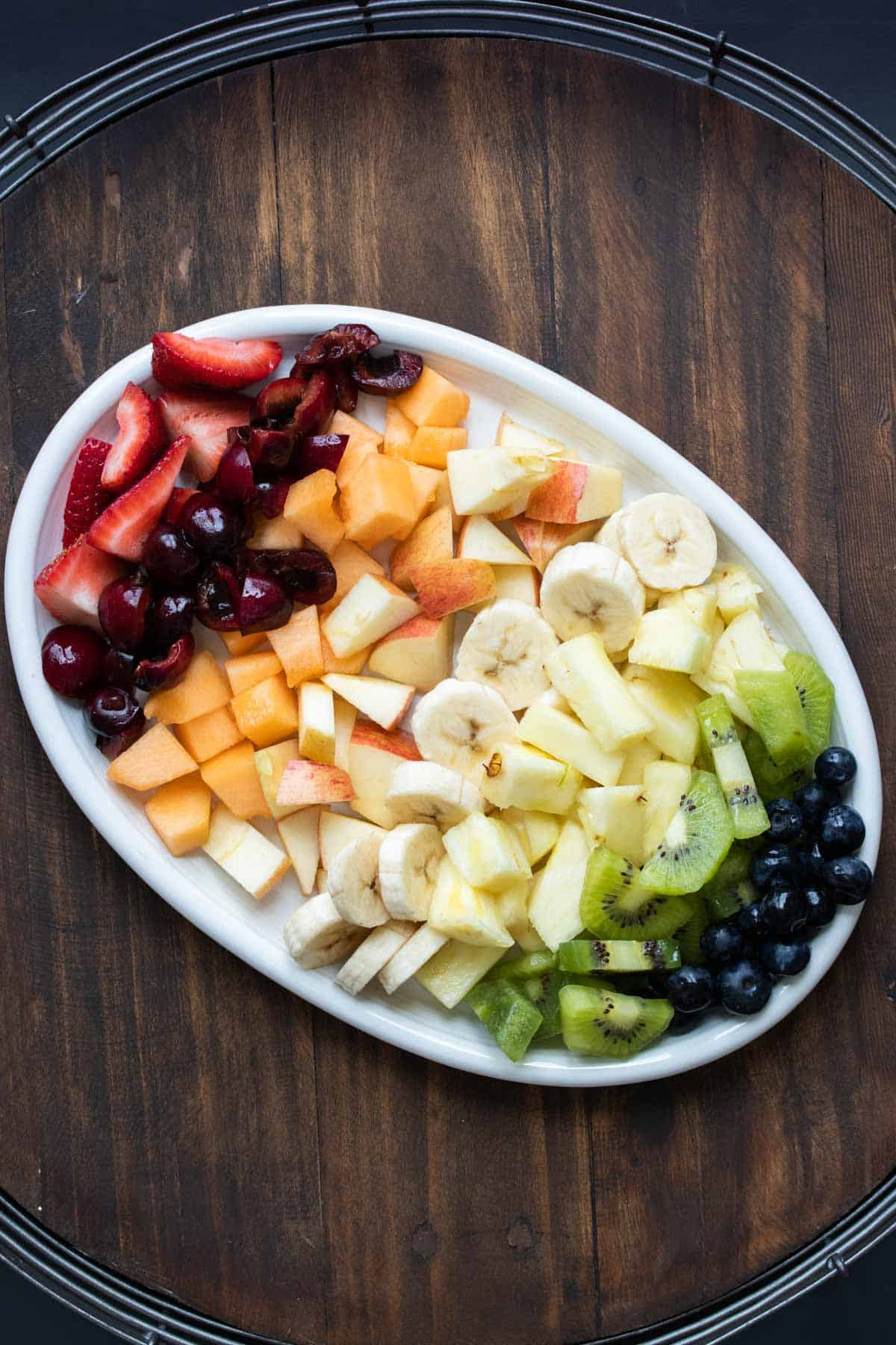 White platter with rows of different cut up fruit