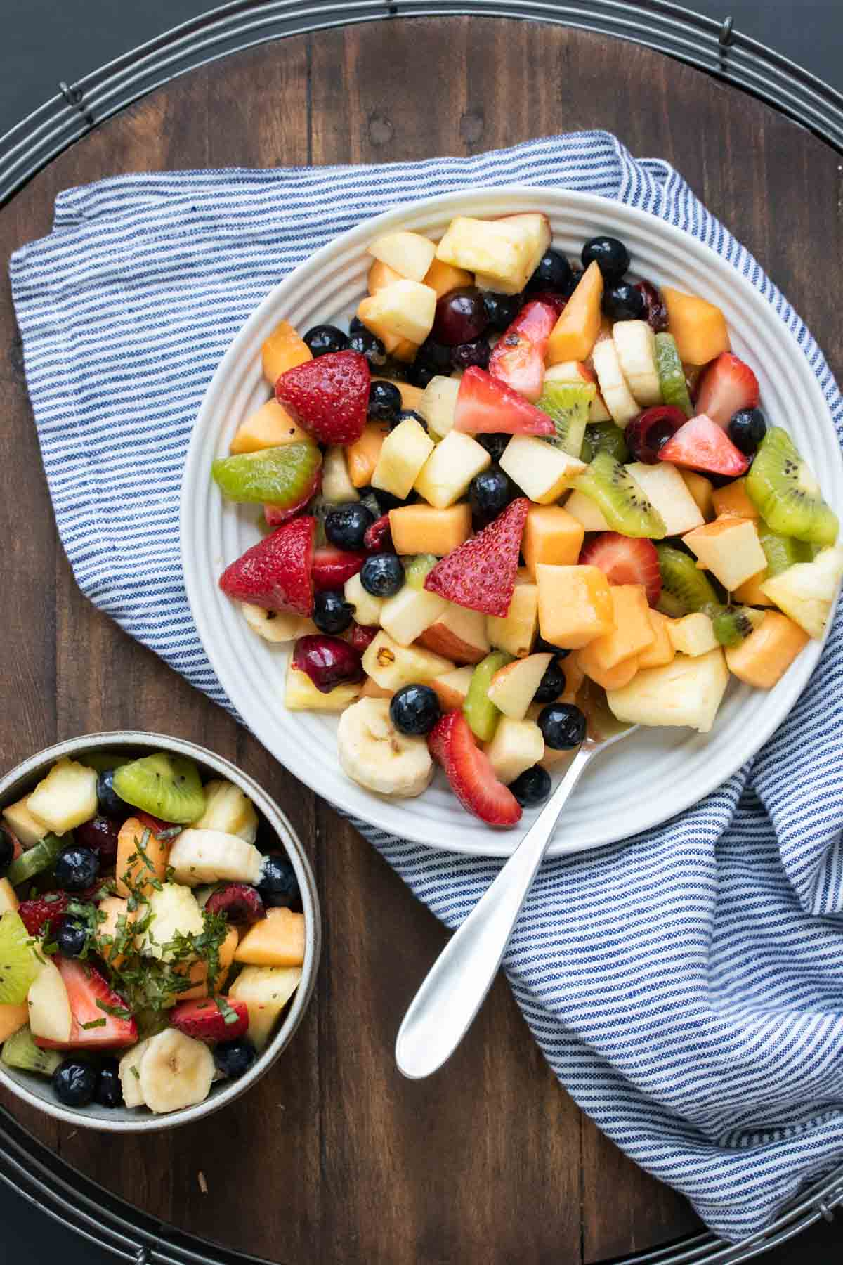 Fruit salad in a bowl next to a plate of it