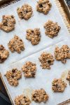 Baked oat breakfast cookies on a piece of parchment on a baking sheet