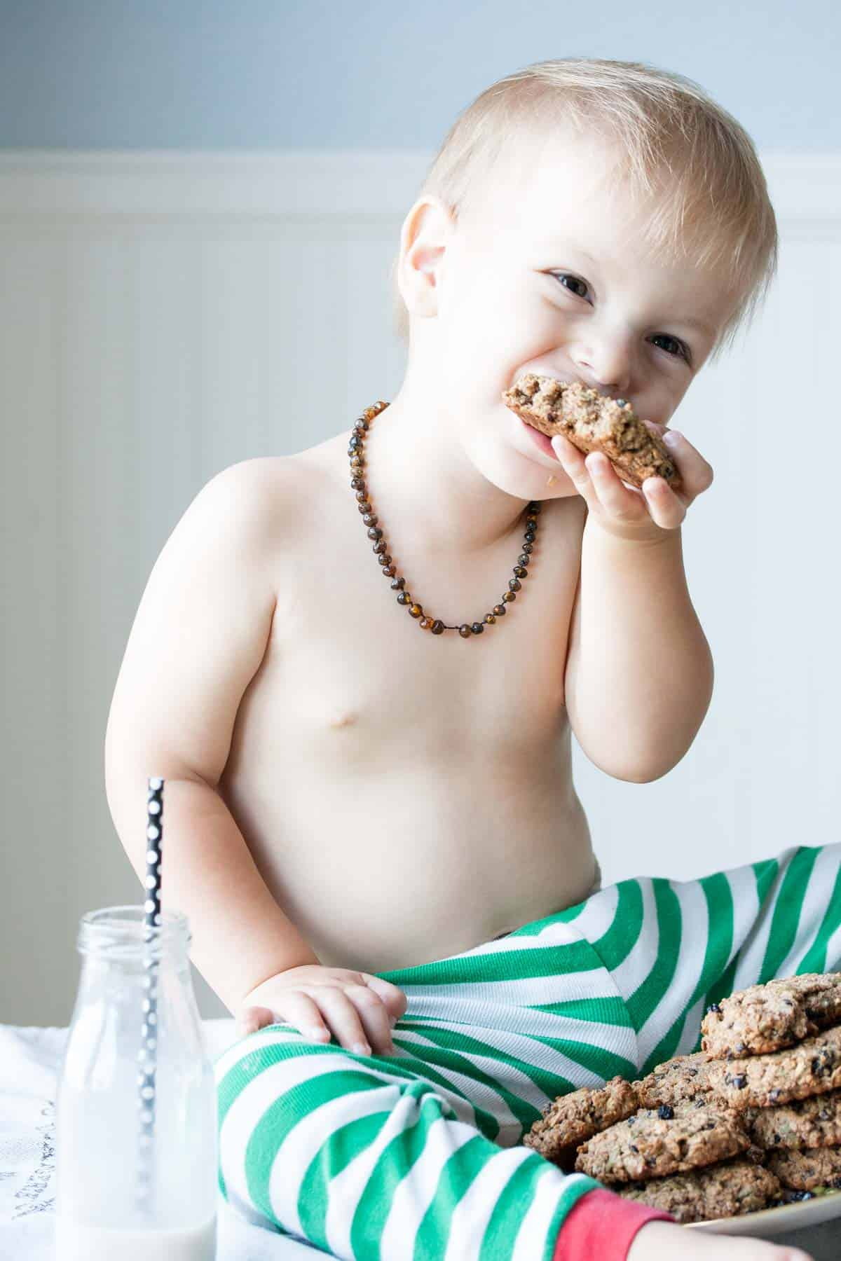 Little boy laughing and eating a cookie