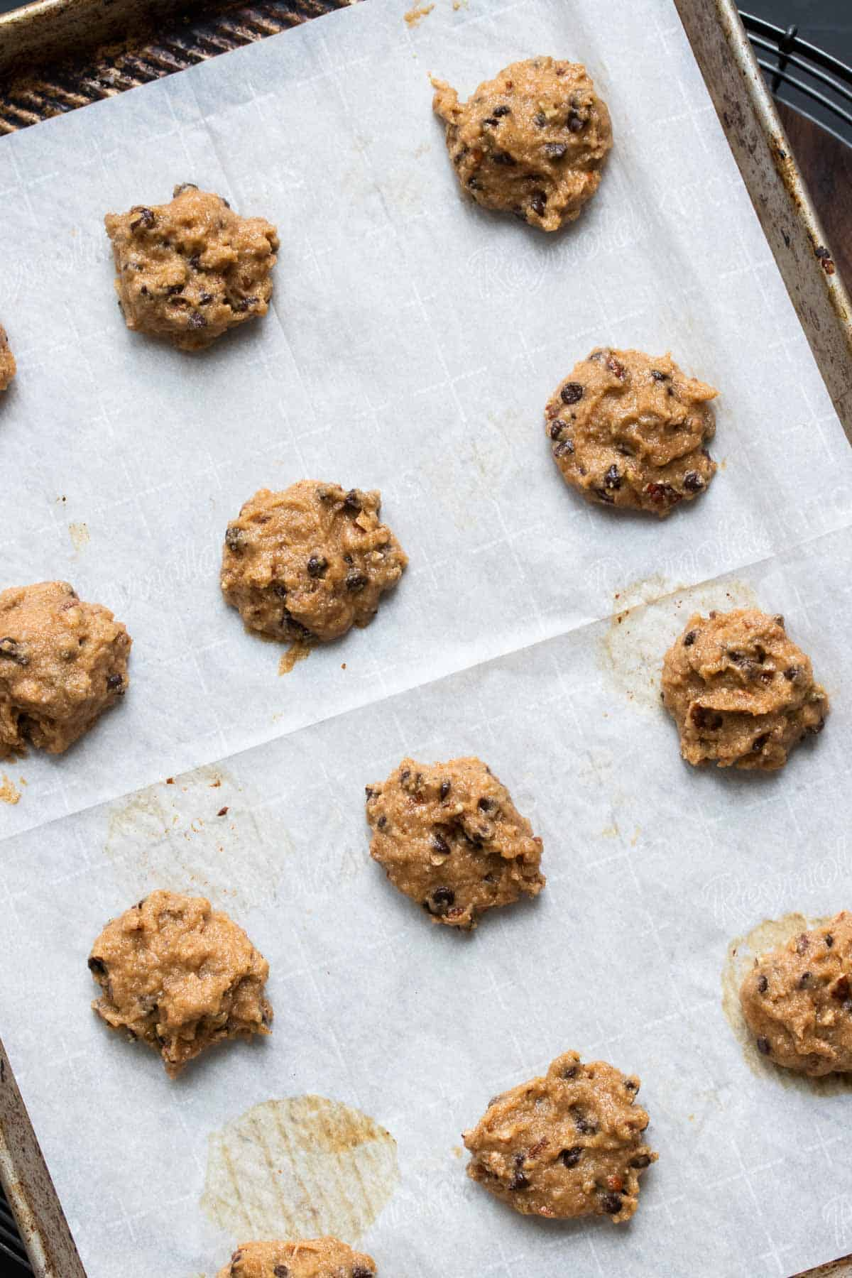 Drops of cookie dough on a parchment lined baking sheet