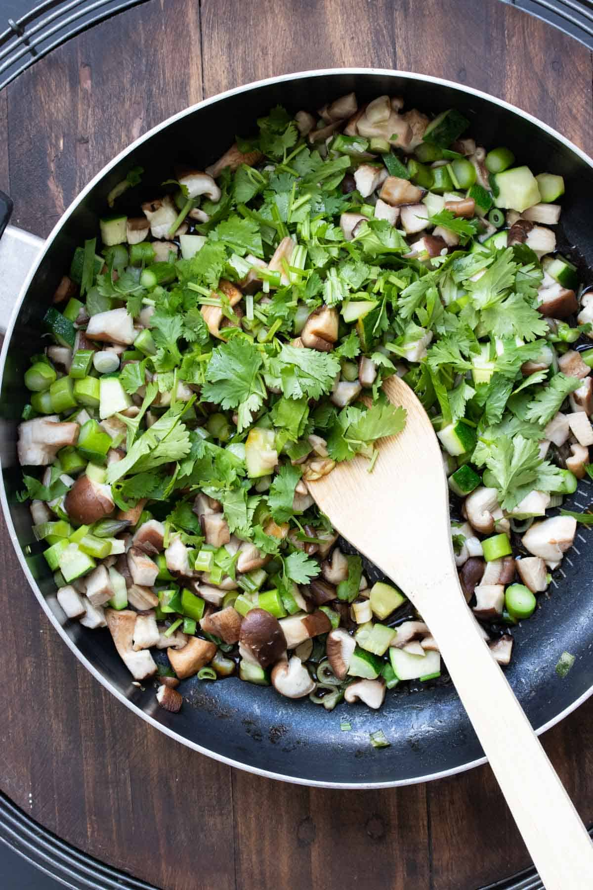 Chopped mushrooms, asparagus and cilantro being mixed in a pan by a wooden spoon