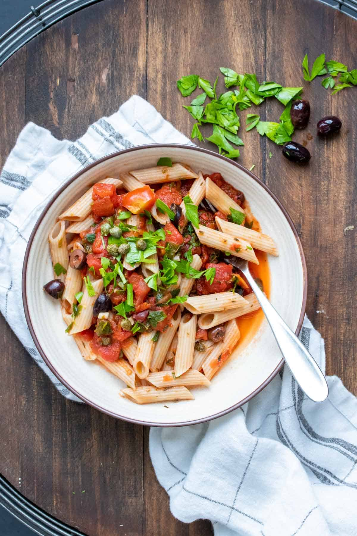 White bowl with penne pasta mixed with puttanesca sauce and parsley