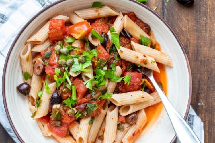 Puttanesca sauce over penne pasta in a white bowl