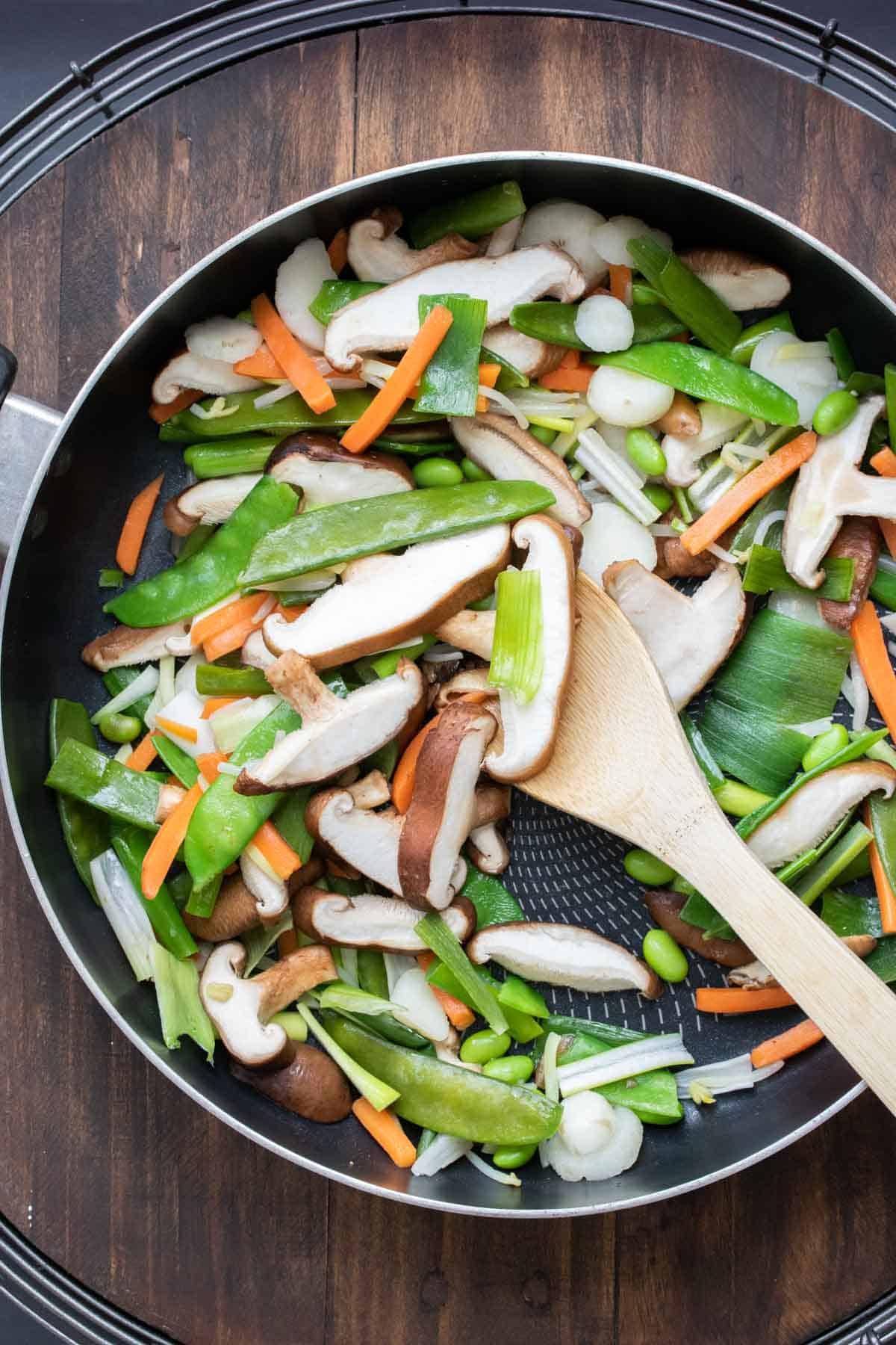 Wooden spoon sautéing veggies in a pan