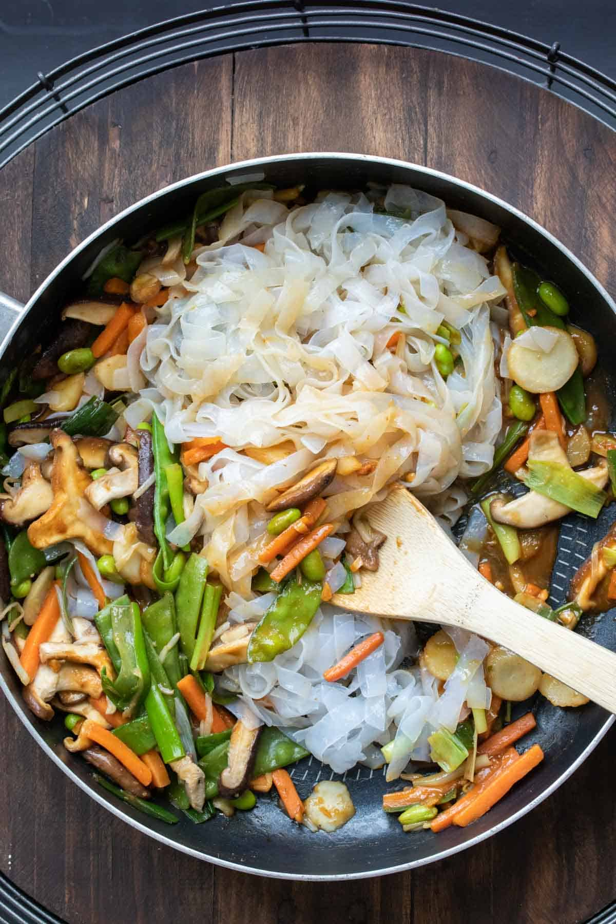 Noodles and veggies mixing with a brown sauce in a pan