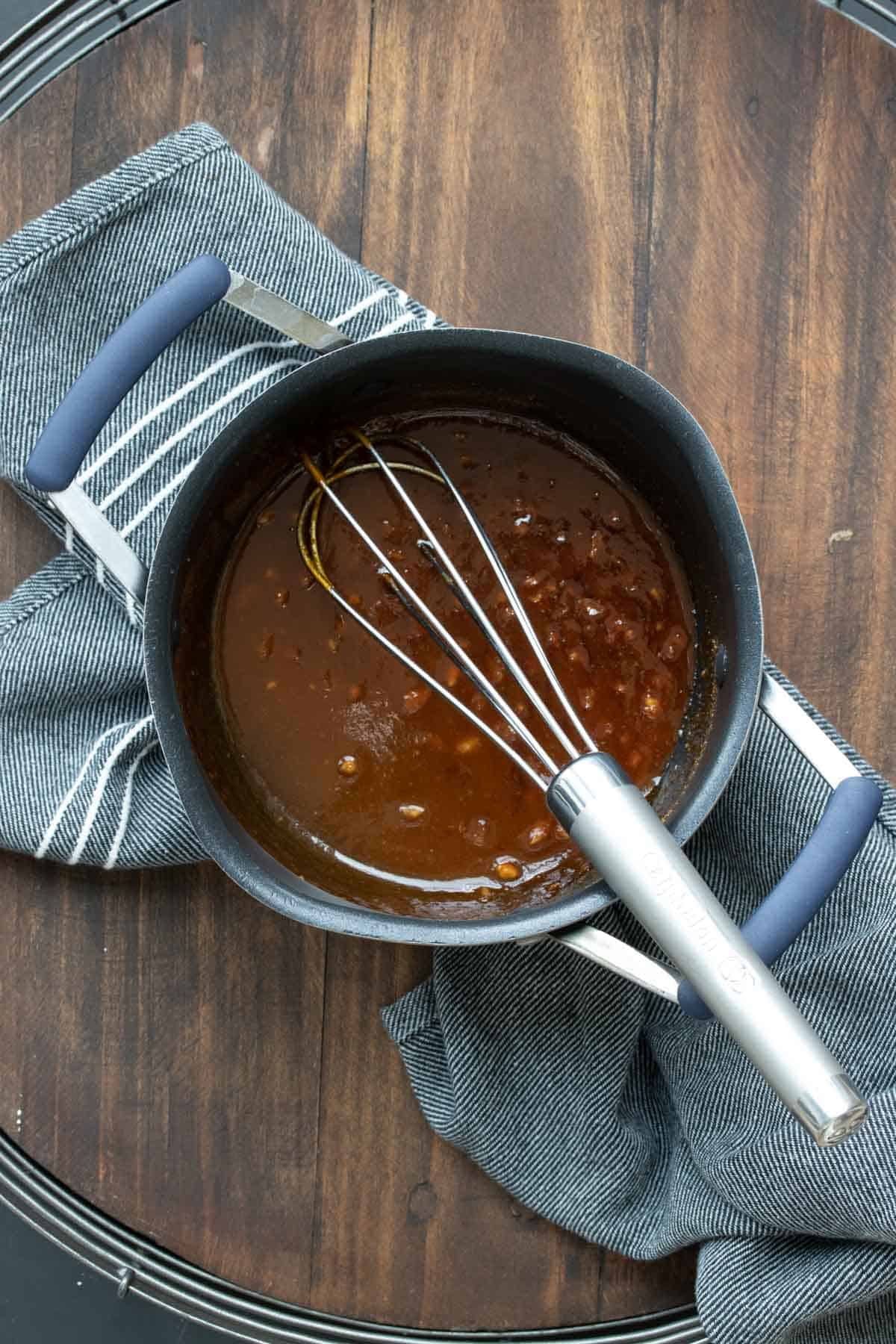 Whisk mixing brown sauce in a pot