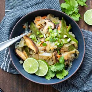 Stir fried noodles and veggies in a dark blue bowl with lime slices and cilantro