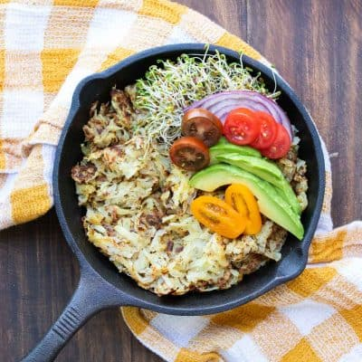 Skillet with cooked hashbrowns and pile of veggies