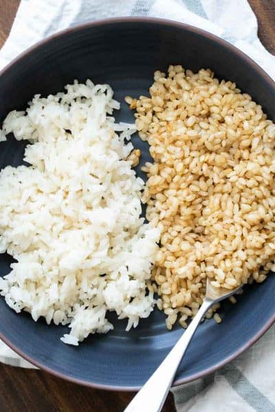 Black bowl filled half with white rice and half with brown rice
